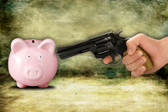 Financial crisis concept. Piggy bank and hand with gun Stock Photography