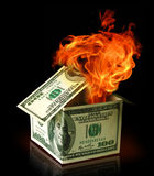 Financial crisis concept. House made of USA dollar bank notes in fire Royalty Free Stock Images