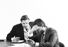 Financial crisis, credit debt, bankruptcy. Men in with tired, worried faces read business news. Business partners in. Formal suits look at smartphone. Business stock photography