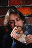 Financial crisis in Europe. Young man lights a cigar with � 50 Royalty Free Stock Images