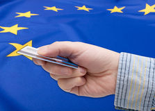 Financial Crisis in Europe. Financial Crisis in Greece - Man's Hand With Banking Card and flag of European Union royalty free stock photo