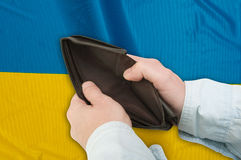 Financial Crisis in Ukraine. Man's Hand With Empty Wallet and Ukrainian flag royalty free stock image
