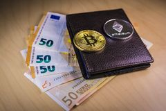 Financial concept with physical bitcoin and ethereum over a wallet with Euro bills stock photos