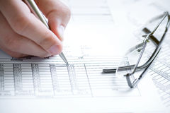 Financial data analyzing. Hand with pen and glasses Royalty Free Stock Images