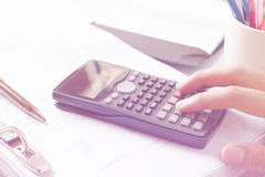 Financial data analyzing. Close-up photo of a businessman's hand counting on calculator in office or home Stock Photo
