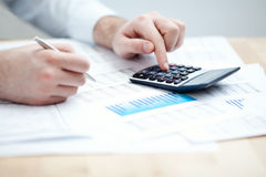 Financial data analyzing. Counting on calculator. Close-up. Selective focus Stock Images