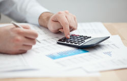 Financial data analyzing. Counting on calculator. Stock Image
