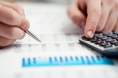 Financial data analyzing. Counting on calculator. Close-up. Selective focus Royalty Free Stock Images