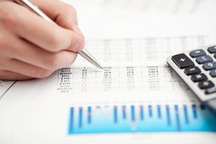 Financial data analyzing. Counting on calculator. Royalty Free Stock Images