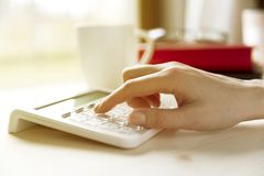 Financial data analyzing hand writing and counting on calculator. At home on wooden desk Stock Images