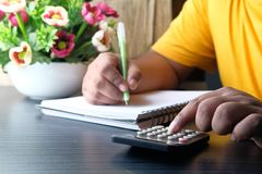 Financial data analyzing hand writing and counting on calculator in office on wood desk Stock Images