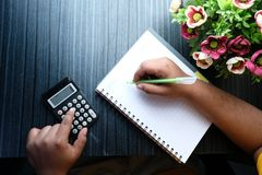 Financial data analyzing hand writing and counting on calculator in office on wood desk Royalty Free Stock Photos