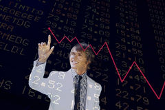 Financial Diagram. Young business man pointing to a chart isolated on black Stock Images