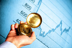 Financial direction. Hand holding a compass with financial graph in background Stock Images