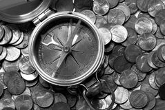 Financial Direction. A black and white image of an old brass nautical compass atop US coins. This portrays business direction and financial success Stock Image