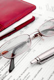 Financial document and notebook. Pen,glasses and notebook close-up Stock Image