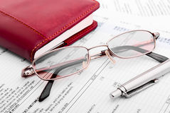 Financial document and notebook. Pen,glasses and notebook close-up Royalty Free Stock Photography