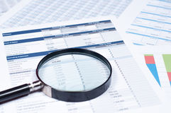 Financial documents. Magnifying glass over financial documents Royalty Free Stock Photos
