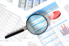 Financial documents. With magnifying glass over them Stock Photography