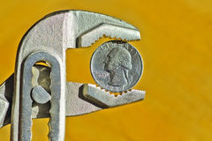 Financial dollar crisis. Close up of an Dollar Coin between pliers, concept of financial dollar crisis Royalty Free Stock Photos