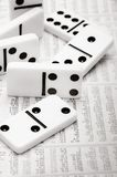 Financial domino. Dominoes pieces on a financial newspaper background Stock Images