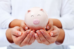 Financial education concept - adult and child hands holding pigg Royalty Free Stock Photography