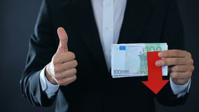 Financial expert holding euro banknotes, showing thumbs up and down, falling stock video footage