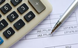 Financial figures. Close up of ballpoint pen and calculator over financial figures Stock Images