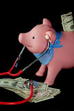 Financial Fitness. Piggy bank with a stethoscope on a pile of money Stock Image