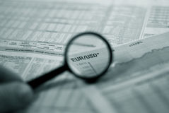 Financial focus. Magnifying glass focusing on a graph and currency pair euro dollar in financial newspaper Stock Photos