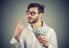 Financial fraud. Liar businessman with dollar cash. Financial fraud concept. Liar business man with dollar cash and long nose royalty free stock photo