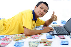 Financial freedom. Man play laptop with smile and money around him stock photo