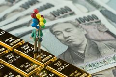 Financial freedom or happy retirement concept, miniature figure. Happy old man holding balloons standing on gold bullion bar and japanese money yen banknotes Stock Photos