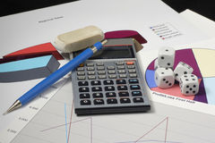 Financial Future. Several pair of dice sit on top of financial charts. There is a calculator, a pencil, and an eraser in the photo.  There is a graph, and two Royalty Free Stock Images