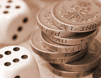 Financial Gamble. UK pound coins and dice Royalty Free Stock Photos