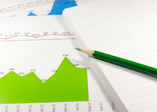 financial graph chart with notebook and green pencil. business c Stock Photography