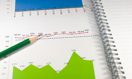 financial graph chart with notebook and green pencil. business c Royalty Free Stock Photos