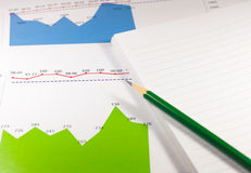 financial graph chart with notebook and green pencil. business c Stock Photos