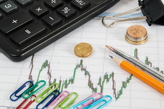Financial graph on a white background with calculator, coins, pens, pencils, paper clips Stock Photos
