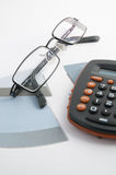 Financial graphics. With glasses and calculator (blue colour Stock Photo
