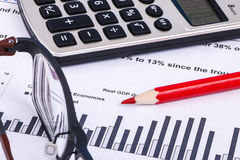 Financial graphs and charts. Financial charts and graphs with calculator, pencil and glass Royalty Free Stock Images