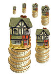 Financial growth. Photo of houses sitting on top of stack of gold coins of varying heights depicting economic growth Royalty Free Stock Photos