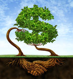 Financial Growth Agreement. With two trees in the shape of a dollar sign and the roots in the form of hands shaking in partnership of a contract deal  for Royalty Free Stock Photo