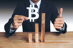 Financial growth concept, Businessman holding showing bitcoin sy. Mbol, concede Rise of price and the continued growth of the business. wooden block of the Stock Images