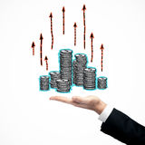 Financial growth concept. Businessman`s hand holding upstratc coin stacks with upward red arrows. Financial growth concept Stock Photography