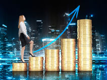 Financial growth concept. With businesswoman walking up golden coin ladder with upward arrow on night city background Royalty Free Stock Images
