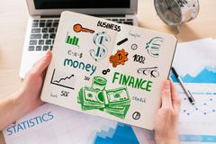 Financial growth concept. Close up of male hands holding notepad with creative finance sketch above workplace with laptop, business report and other items Royalty Free Stock Photos