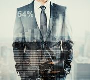 Financial growth concept. Front view of young businessman on abstract city background with business chart. Financial growth concept. Double exposure Royalty Free Stock Photo