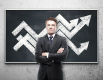Financial growth concept. Handsome young businessman with chart arrows on blackboard. Financial growth concept Stock Images