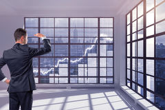 Financial growth concept. Handsome young businessman in interior looking out of window with city and abstract business chart bars view. Financial growth concept stock photos